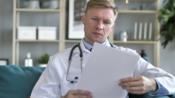 A doctor looking at result paper