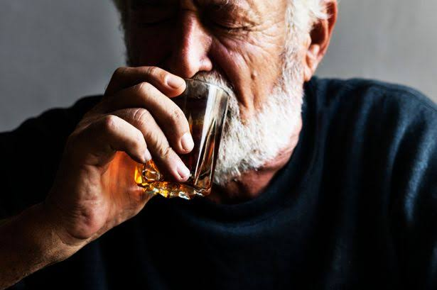 An old man drinking alcohol