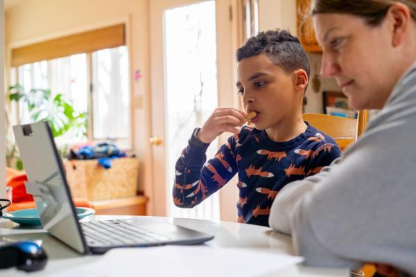 A child pressing laptop with his father