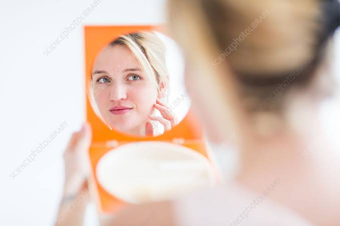 A lady checking her face on a mirror