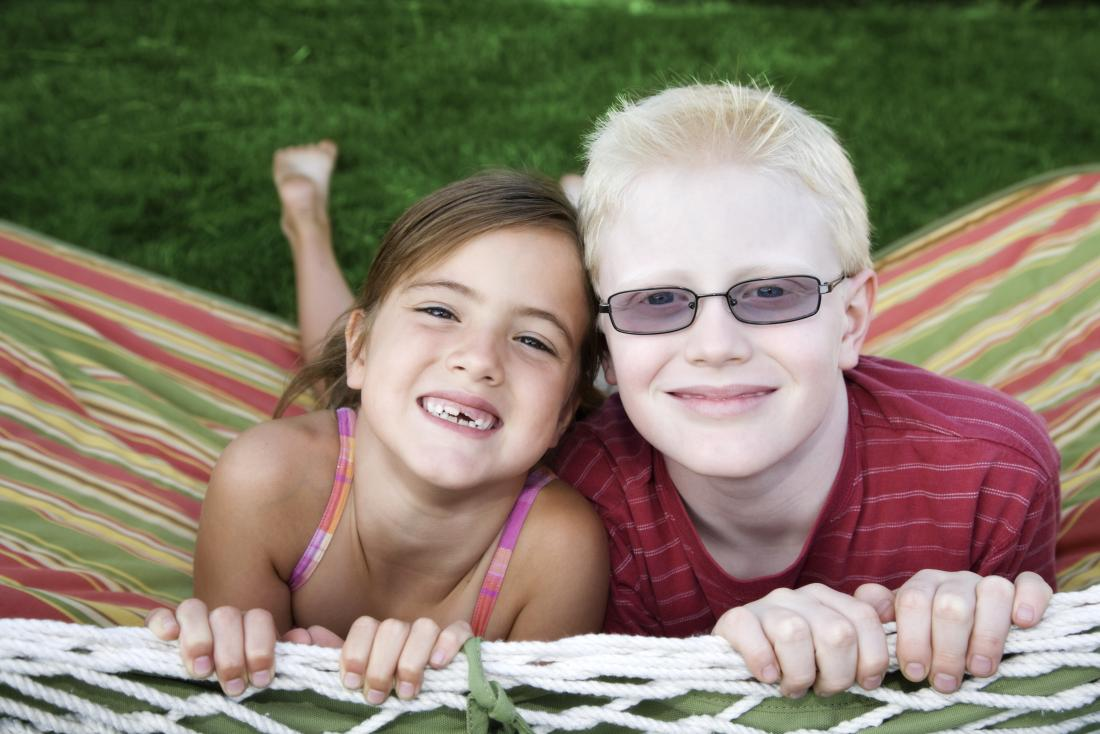 Young boy with albinism, next to young girl with normal skin pigmentation.
